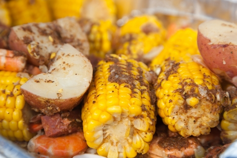 A traditional low country boil with red potatoes, corn on the cob, and shrimp. Everything is seasoned to perfection with cajun spices.
